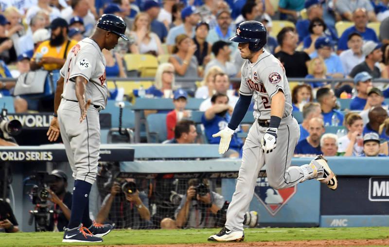 Oct 24, 2017; Los Angeles, CA, USA; Houston Astros third baseman Alex Bregman (2) celebrates with third base coach Gary Pettis (8) as he runs home on a solo home run against the Los Angeles Dodger ...