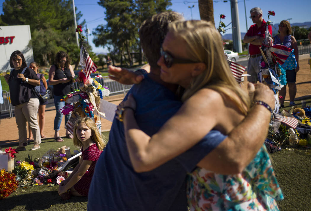 Robert Patterson, center left, of Lomita, California, gets a hug from a stranger as daughter Brooke, 7, looks on while visiting the makeshift memorial for Lisa Patterson, who was one of 58 people  ...