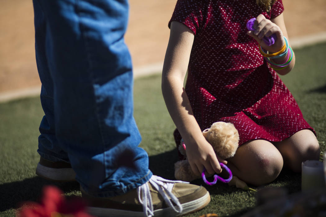 Seven-year-old Brooke Patterson of Lomita, California, holds items found while visiting a makeshift memorial for her mother, Lisa Patterson, who was one of 58 people who died in the Oct. 1 shootin ...