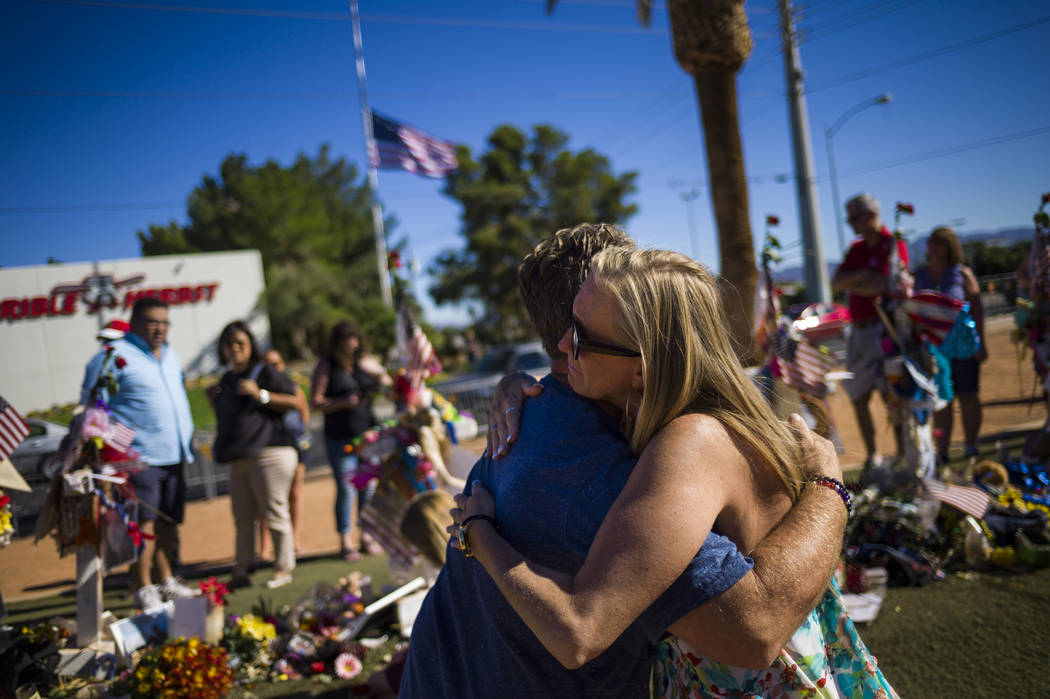 Robert Patterson of Lomita, California, gets a hug from a stranger while visiting the makeshift memorial for his wife, Lisa Patterson, who was one of 58 people who died in the Oct. 1 shooting at a ...