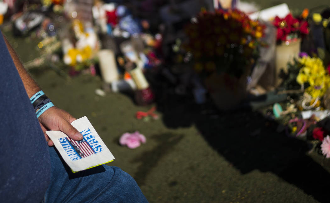 Robert Patterson of Lomita, California, holds a card found at the makeshift memorial for his wife, Lisa Patterson, who was one of 58 people who died in the Oct. 1 shooting at a music festival, nea ...