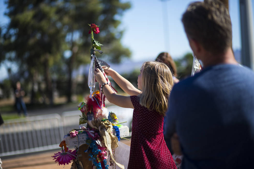 Robert Patterson, right, of Lomita, California, and daughter Brooke, 7, visit the makeshift memorial for wife and mother Lisa Patterson, who was one of 58 people who died in the Oct. 1 shooting at ...