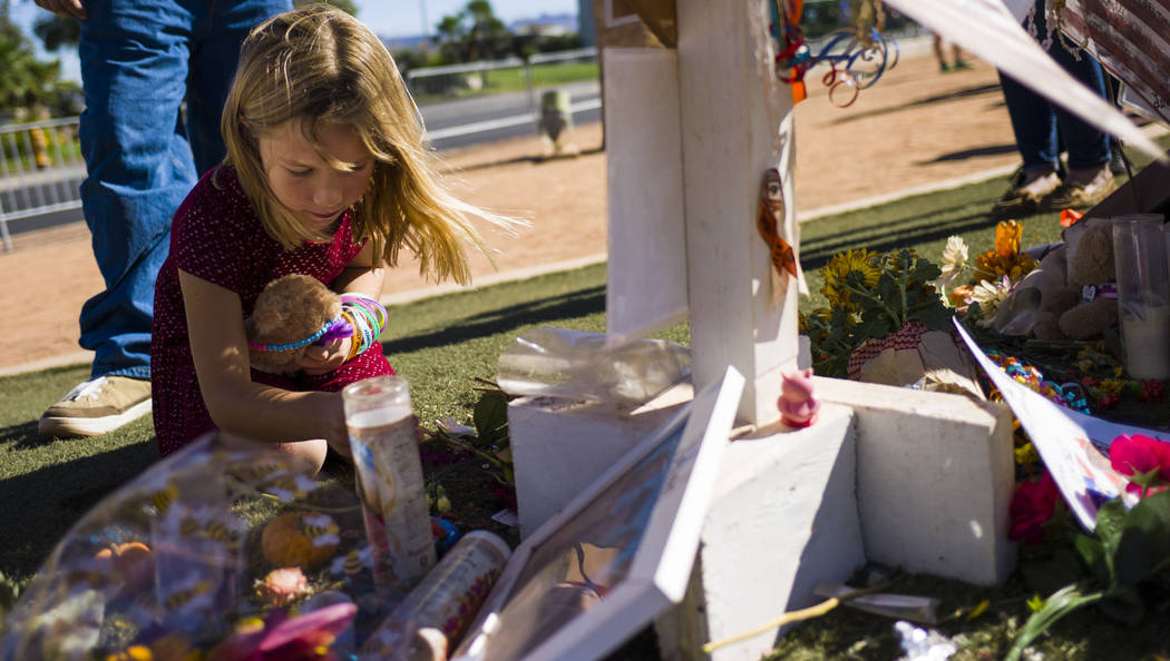 Seven-year-old Brooke Patterson of Lomita, California, looks through items left at a makeshift memorial for her mother, Lisa Patterson, who was one of 58 people who died in the Oct. 1 shooting at  ...