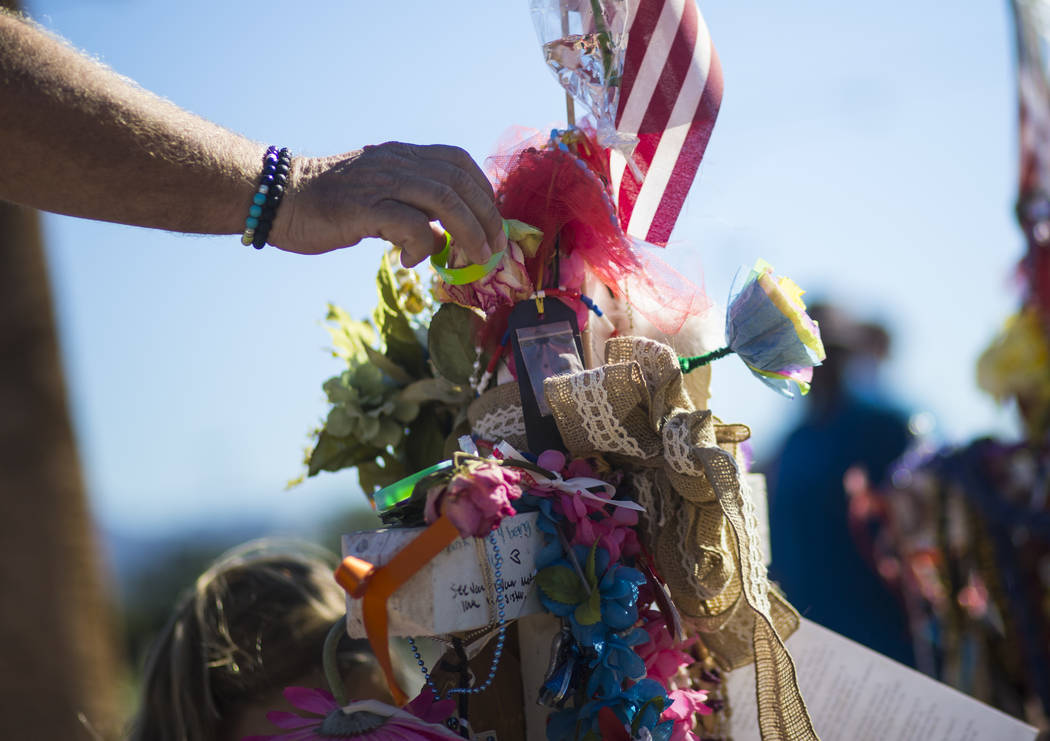 Robert Patterson of Lomita, California, leaves a bracelet at the makeshift memorial for his wife, Lisa Patterson, who was one of 58 people who died in the Oct. 1 shooting at a music festival, near ...