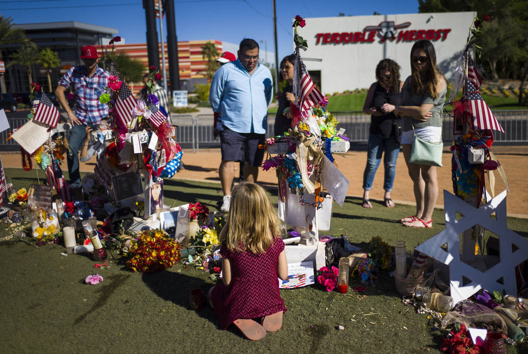 Seven-year-old Brooke Patterson of Lomita, California, center, visits a makeshift memorial for her mother, Lisa Patterson, who was one of 58 people who died in the Oct. 1 shooting at a music festi ...