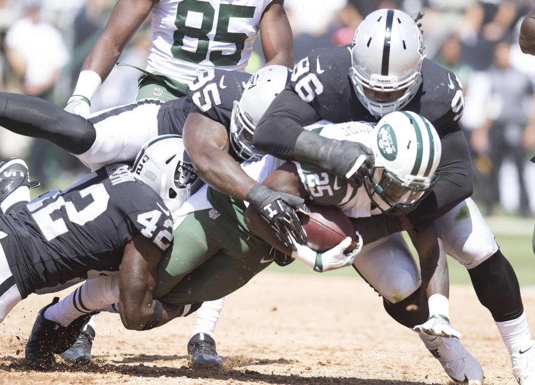 New York Jets running back Elijah McGuire is tackled by Oakland Raiders defensive end Denico Autry (96) defensive end Jihad Ward (95) and strong safety Karl Joseph (42) in the first half of their  ...