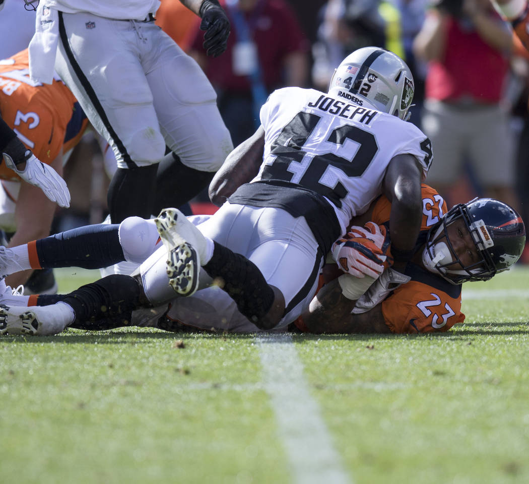 Oakland Raiders strong safety Karl Joseph (42) tackles Denver Broncos running back Devontae Booker (23) in the first half of their game in Denver, Colo., Sunday, Oct. 1, 2017. Heidi Fang Las Vegas ...