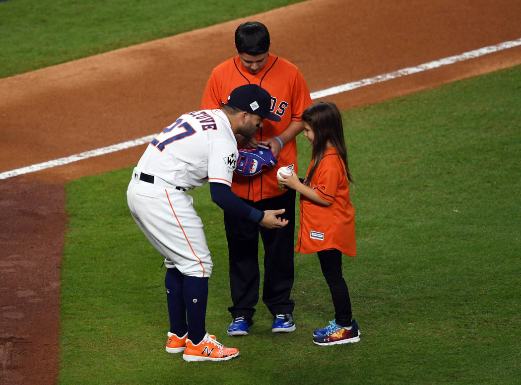 Oct 28, 2017; Houston, TX, USA; Hailey Dawson (right) greets Houston Astros second baseman Jose Altuve (27) after throwing out for the ceremonial first pitch before game four of the 2017 World Ser ...