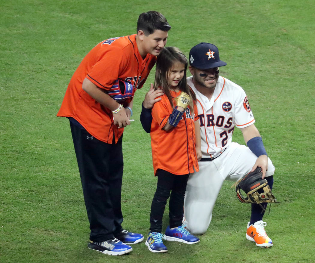 Oct 28, 2017; Houston, TX, USA; Hailey Dawson (middle) poses with Houston Astros second baseman Jose Altuve (27) after throwing out the ceremonial first pitch before game four of the 2017 World Se ...