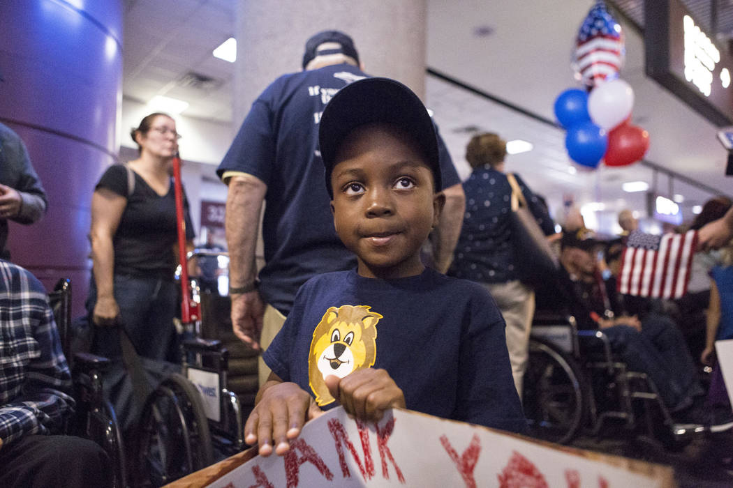 Boy Scout Cyril Schoubert, 5, holds a sign welcoming a World War II and Korean War Veterans at McCarran International Airport after they return to Las Vegas from Washington, D.C. from an Honor Fli ...