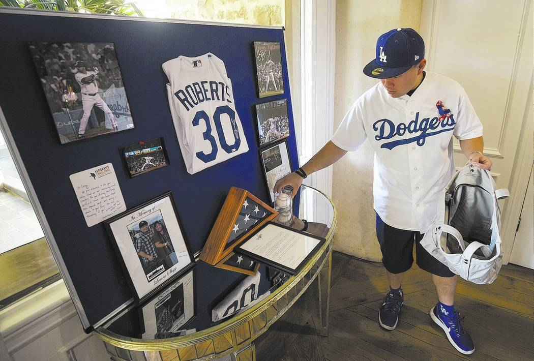 Corey Shipp, son of Route 91 Harvest shooting victim Laura Shipp, prepares a display of Los Angeles Dodgers memorabilia honoring his mother's love for baseball and the Dodgers during a memorial se ...