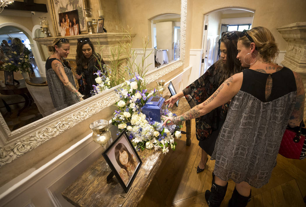 Jill Boelman, right, and Nancy Treichler visit the urn bearing the remains of Route 91 Harvest shooting victim Laura Shipp during a memorial service for Shipp in Westlake Village, Calif., Sunday,  ...