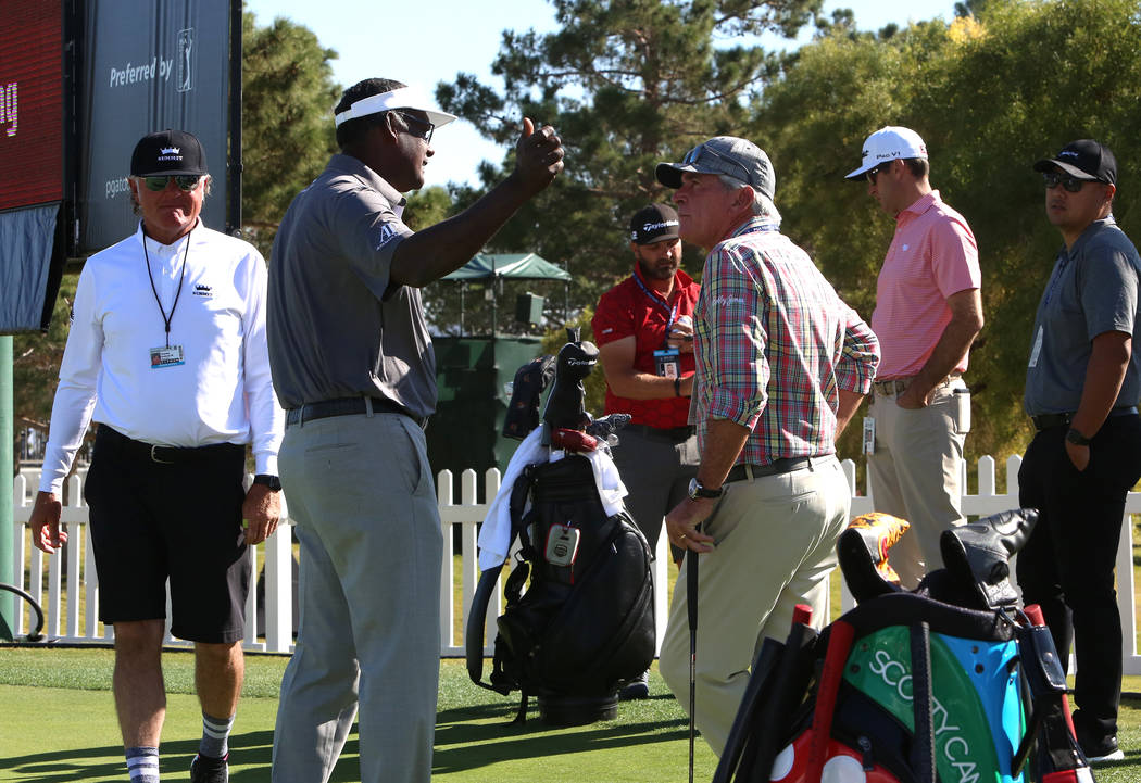 Vijay Singh of Fiji, second left, talks to Tommy Armour, left, and Marius Filmalter after practicing their putting as they prepare for the Shrine Hospitals for Children Open golf tournament at TPC ...
