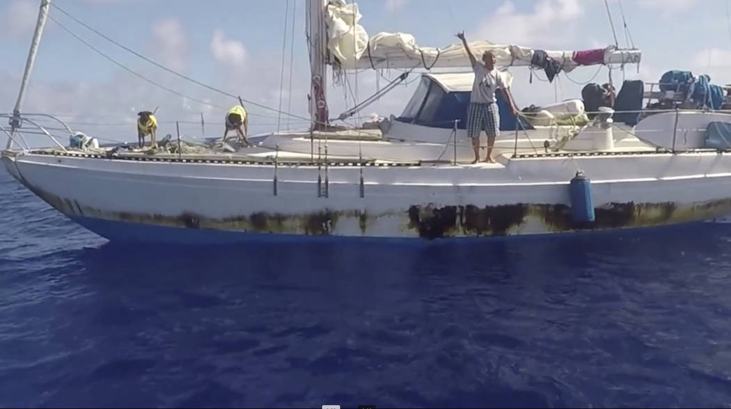 In this Wednesday, Oct. 25, 2017 still image taken from video provided by the U.S. Navy, Jennifer Appel, of Honolulu, holds up a shaka sign as rescuers approach her crippled sailboat, the Sea Nymp ...