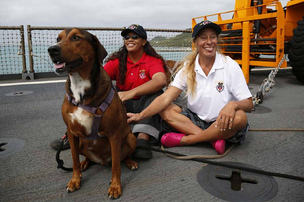 Jennifer Appel, right, and Tasha Fuiava sit with their dogs on the deck of the USS Ashland Monday, Oct. 30, 2017,  at White Beach Naval Facility in Okinawa, Japan.  The U.S. Navy ship arrived at t ...