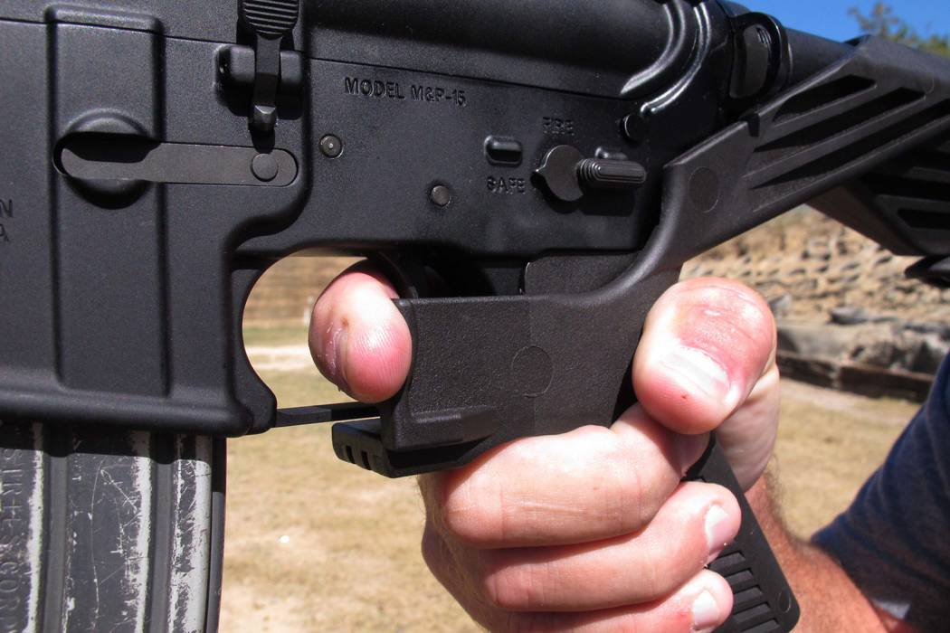"""Shooting instructor Frankie McRae illustrates the grip on an AR-15 rifle fitted with a """"bump stock"""" at his 37 PSR Gun Club in Bunnlevel, N.C., on Wednesday, Oct. 4, 2017. The stock uses the recoil ..."""