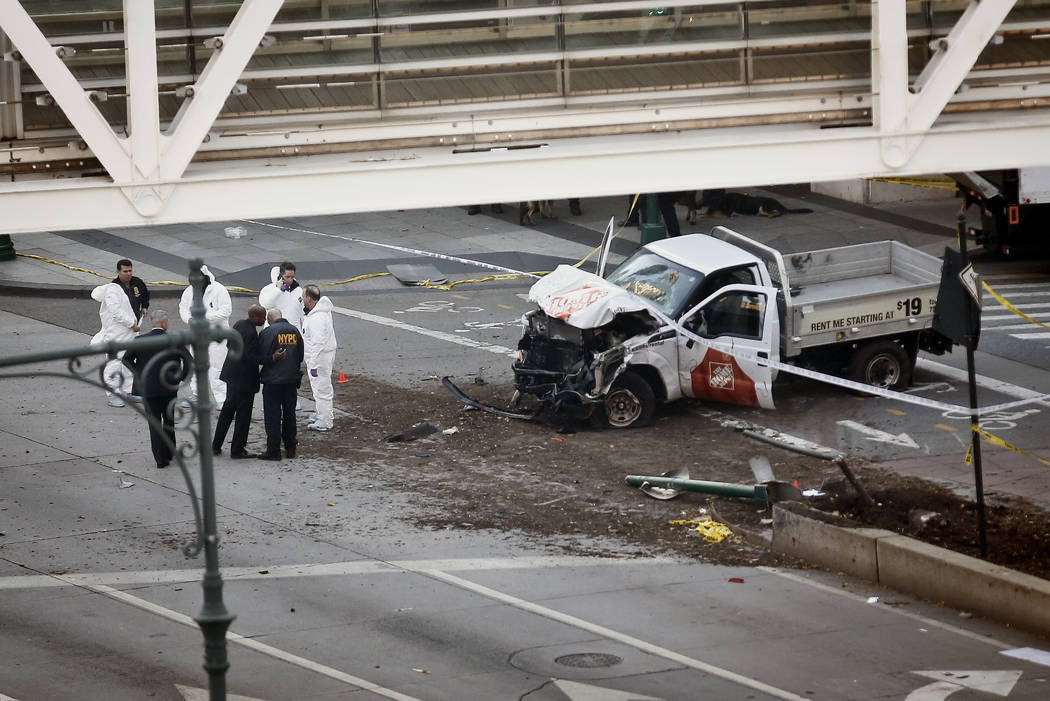 Authorities stand near a damaged Home Depot truck after a motorist drove onto a bike path near the World Trade Center memorial, striking and killing several people Tuesday, Oct. 31, 2017, in New Y ...