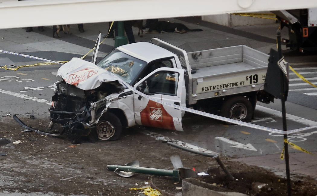 Police tape rests on a damaged Home Depot truck sits after a motorist drove onto a bike path near the World Trade Center memorial, striking and killing several people Tuesday, Oct. 31, 2017, in Ne ...