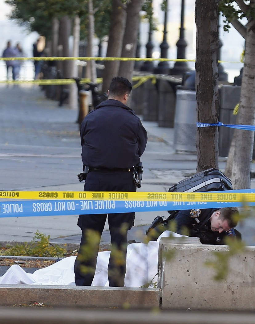 A paramedic looks at a body covered under a white sheet along the bike path Tuesday Oct. 31, 2017, in New York. (AP Photo/Bebeto Matthews)