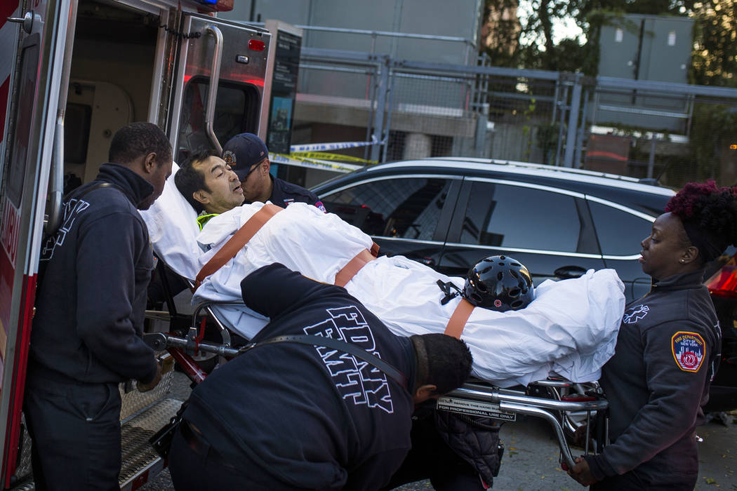 Emergency personnel carry a man into an ambulance after a motorist drove onto a busy bicycle path near the World Trade Center memorial and struck several people Tuesday, Oct. 31, 2017, in New York ...