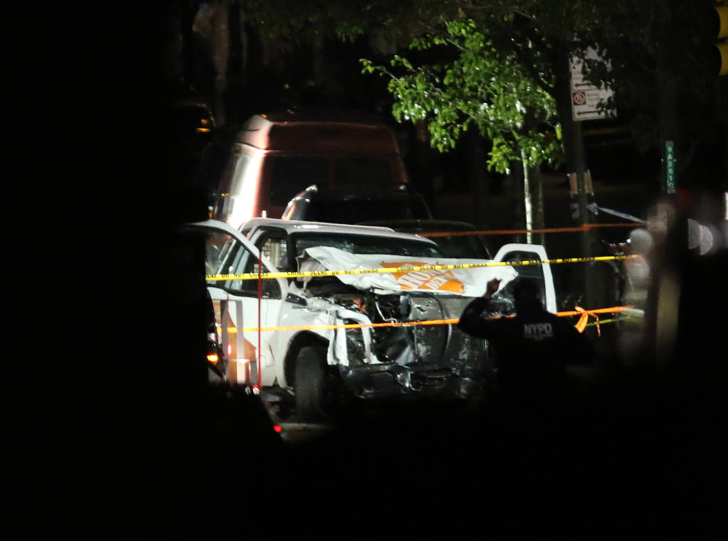 Authorities investigate near a rented Home Depot truck used to mow down pedestrians and cyclists along a busy bike path near the World Trade Center memorial on Tuesday, Oct. 31, 2017, killing at l ...