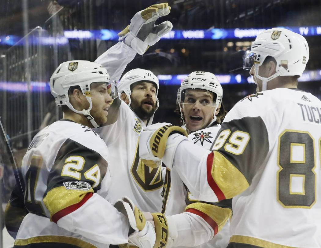 Vegas Golden Knights' Oscar Lindberg (24) celebrates his goal with teammates Alex Tuch (89) and Erik Haula (56) after scoring during the first period of an NHL hockey game against the New York Ran ...