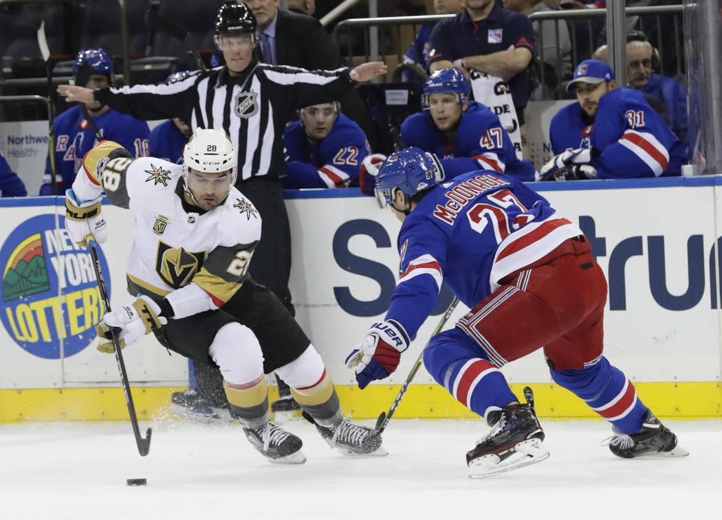 Vegas Golden Knights' William Carrier (28) and New York Rangers' Ryan McDonagh (27) fights for control of the puck during the first period of an NHL hockey game Tuesday, Oct. 31, 2017, in New York ...