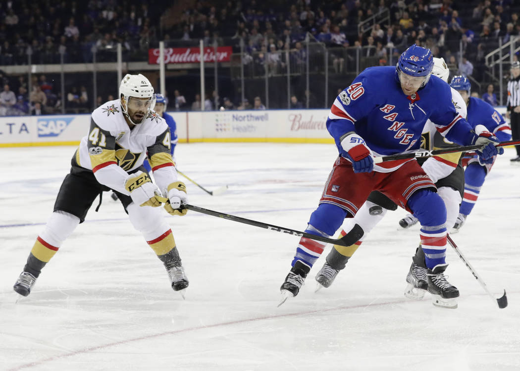 Vegas Golden Knights' Pierre-Edouard Bellemare (41) and New York Rangers' Michael Grabner (40) fight for control of the puck during the second period of an NHL hockey game Tuesday, Oct. 31, 2017,  ...