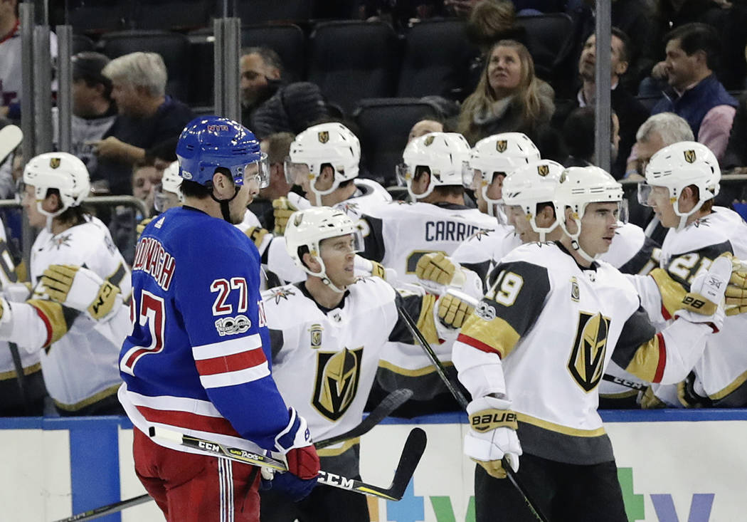 Vegas Golden Knights right wing Reilly Smith (19) celebrates with teammates after scoring a goal as New York Rangers' Ryan McDonagh (27) skates past them during the second period of an NHL hockey  ...