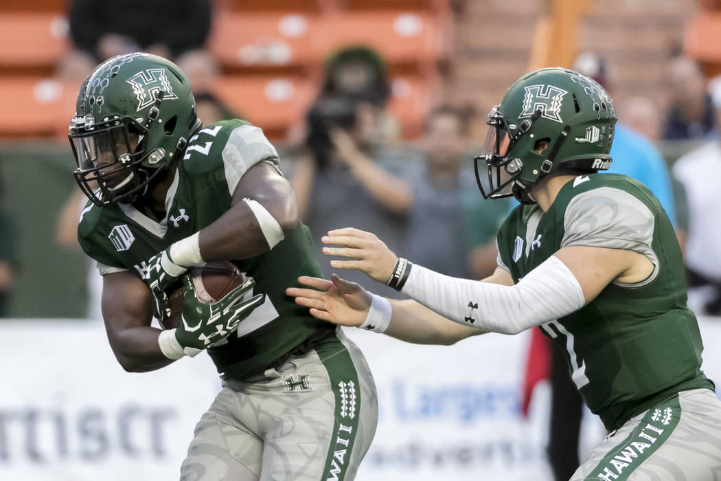 Hawaii quarterback Dru Brown, right, hands off the football to running back Diocemy Saint Juste (22) in the first quarter of an NCAA college football game against San Diego State, Saturday, Oct. 2 ...