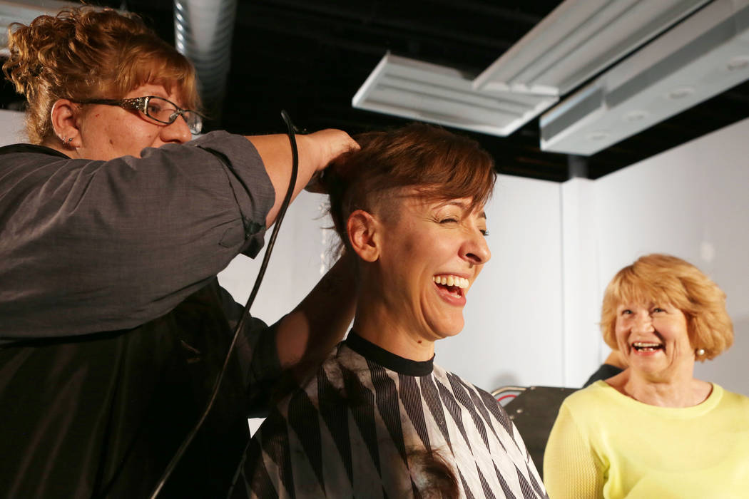 Shawna Brereton shaves the lead actress of Wit Tina Rice's hair while Women's Cancer Center of Nevada and an ovarian cancer patient Virginia Tanedal watches during practice at A Public Fit Theatre ...
