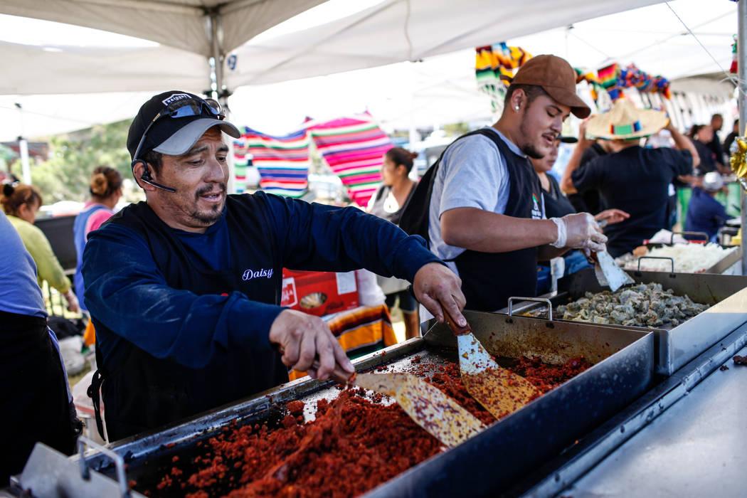 Luis Alberto Rios, 40, left, and Erik Chavez, 22, right, both of Las Vegas, work a booth for Vegas Valli Taqueria at the Original LV Project Taco festival in North Las Vegas, Saturday, Nov. 4, 201 ...