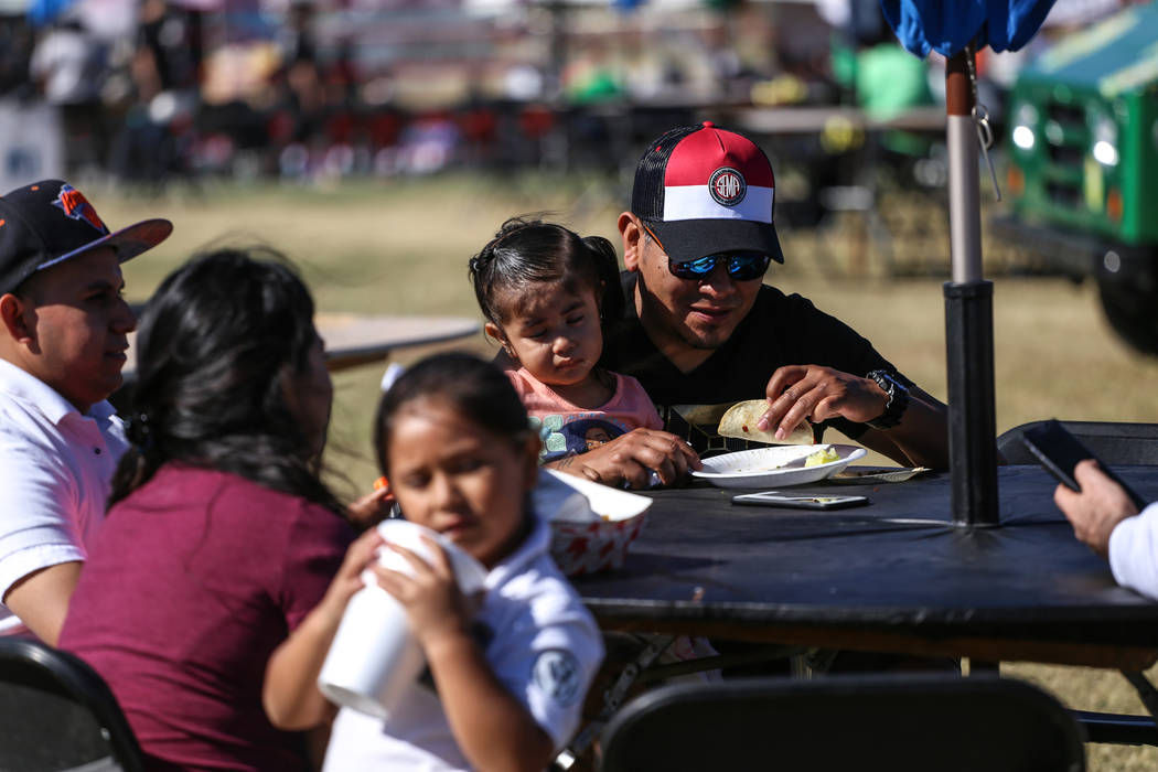 Cesar Gutierrez, 45, right, eats tacos as his daughter Stefania, 2, both of Las Vegas, sits on his lap at the Original LV Project Taco festival in North Las Vegas, Saturday, Nov. 4, 2017. Joel Ang ...