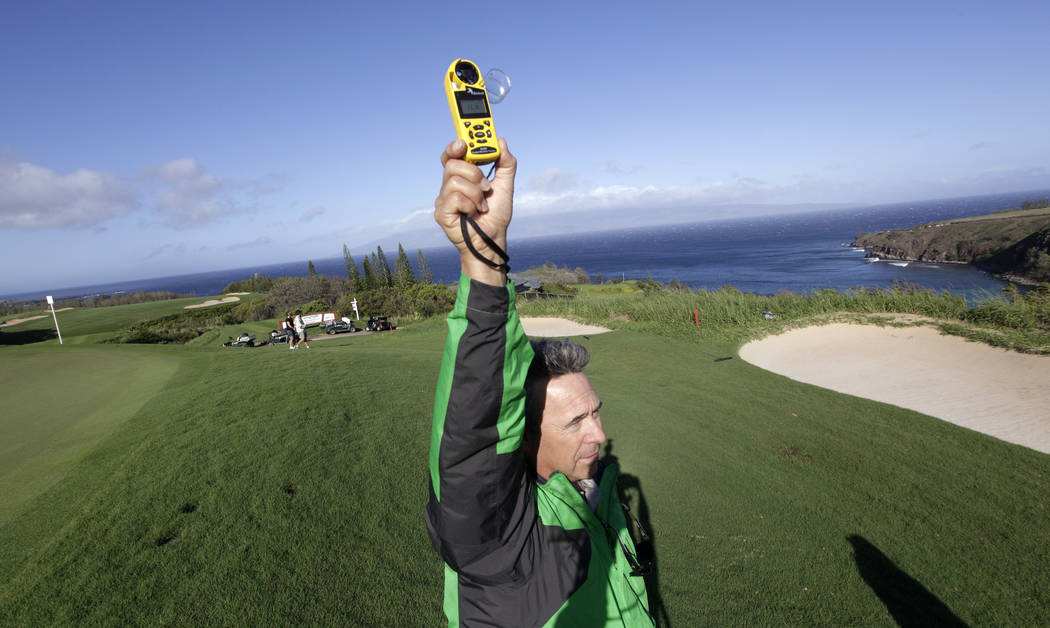 NBC-Golf Channel's John Boeddeker holds up a wind gauge on the 11th green before the first round at the Tournament of Champions PGA golf tournament on Sunday, Jan. 6, 2013, in Kapalua, Hawaii. Pla ...