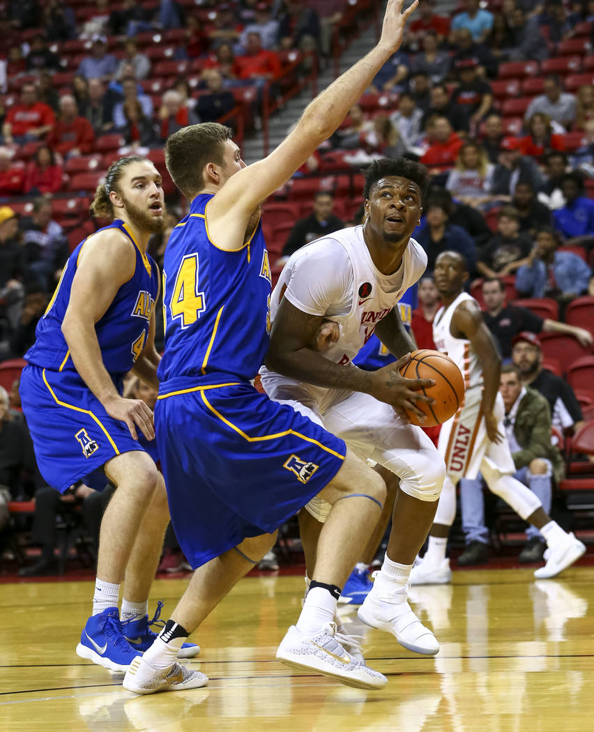 UNLV Rebels forward Tervell Beck, right, looks for a shot under pressure from Alaska Nanooks defenders Daulton Lootens, center, and Michael Kluting during an exhibition basketball game at the Thom ...