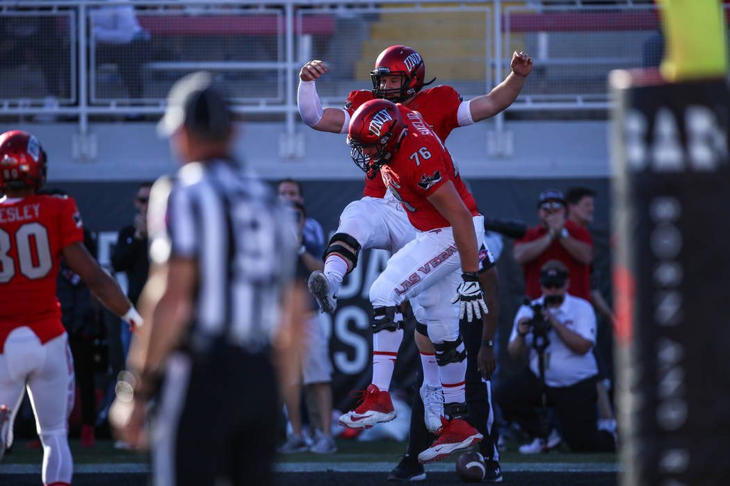 UNLV Rebels quarterback Johnny Stanton (4), left, celebrates with UNLV Rebels offensive lineman Kyle Saxelid (76), right, after scoring a touchdown against the Hawaii Warriors during the first qua ...