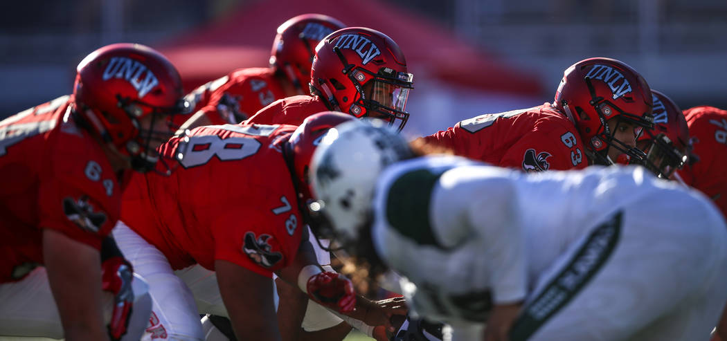 UNLV Rebels quarterback Armani Rogers (1), center, prepares to hike the ball during the first quarter of a football game against the Hawaii Warriors at Sam Boyd Stadium in Las Vegas, Saturday, Nov ...