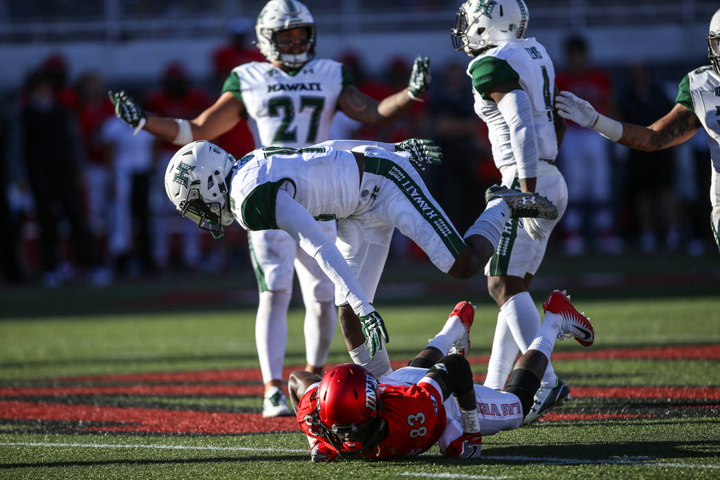 UNLV Rebels wide receiver Devonte Boyd (83), bottom, hits the ground after an incomplete pass against the Hawaii Warriors during the second quarter of a football game at Sam Boyd Stadium in Las Ve ...