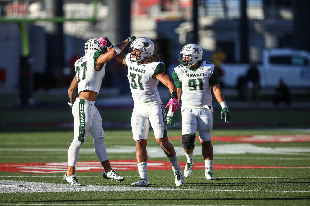 Hawaii Warriors linebacker Solomon Matautia (27), left, and Hawaii Warriors linebacker Jahlani Tavai (31), center, celebrate after a tackle during the second quarter of a football game against the ...