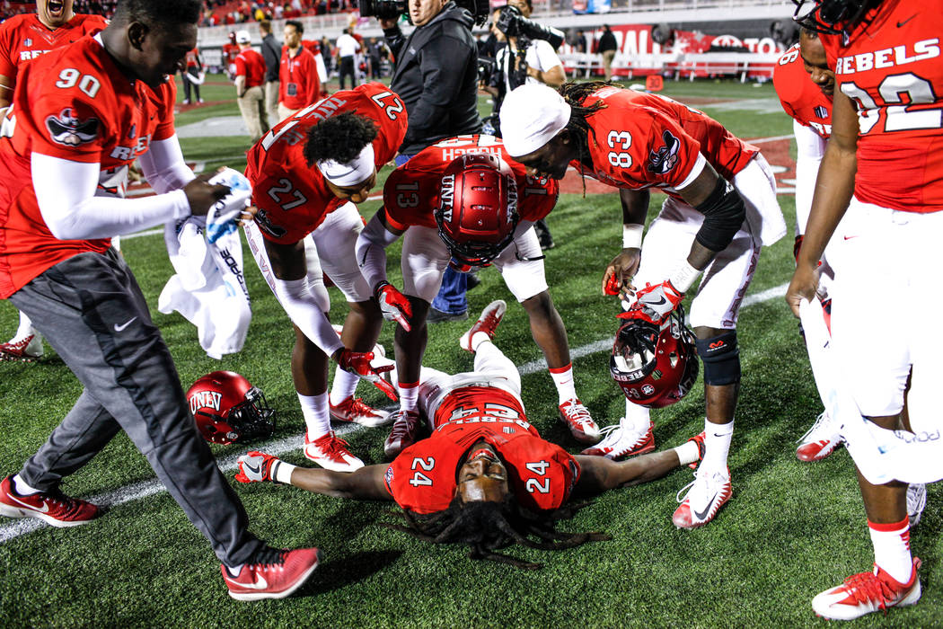 UNLV Rebels defensive back Robert Jackson (24) lies on the ground as teammates celebrate after defeating the Hawaii Warriors 31-23 at Sam Boyd Stadium in Las Vegas, Saturday, Nov. 4, 2017. Joel An ...