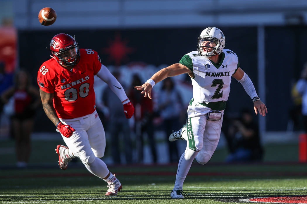 Hawaii Warriors quarterback Dru Brown (2), right, lobs the ball to a teammate during the first quarter of a football game at Sam Boyd Stadium in Las Vegas, Saturday, Nov. 4, 2017. UNLV won 31-23.  ...