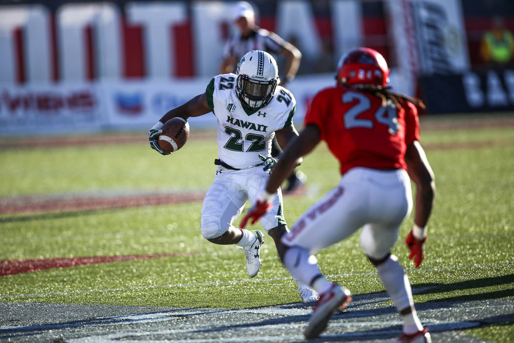 Hawaii Warriors running back Diocemy Saint Juste (22), left, runs the ball against UNLV Rebels defensive back Robert Jackson (24), right, during the second quarter of a football game at Sam Boyd S ...