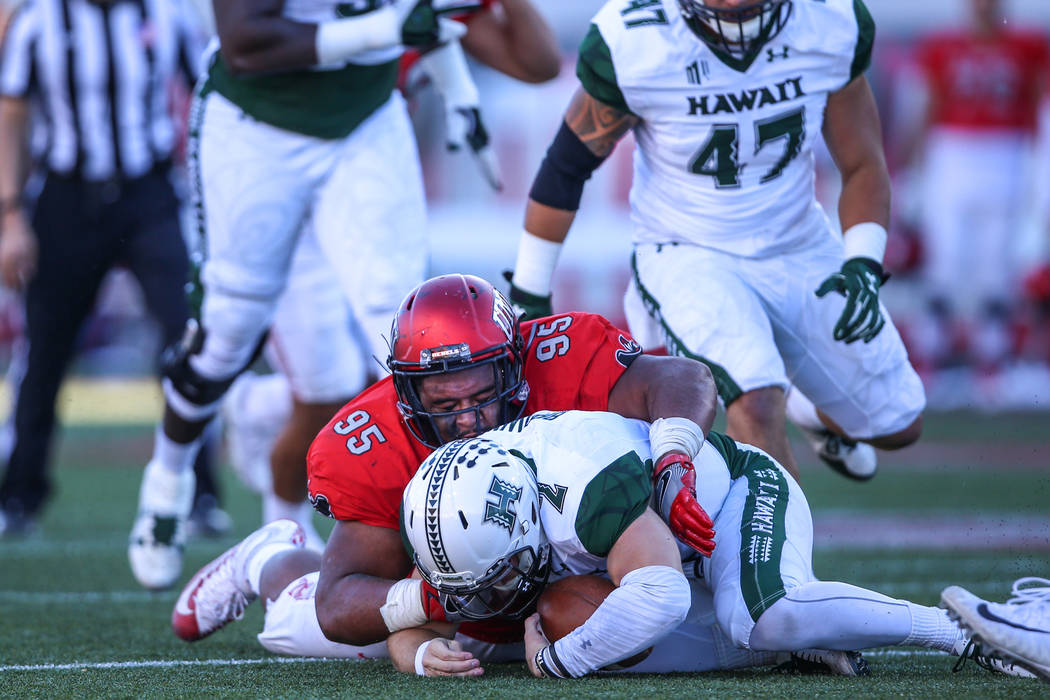 Hawaii Warriors quarterback Dru Brown (2), bottom, is tackled by UNLV Rebels defensive lineman Jason Fao (95), top, during the second quarter of a football game at Sam Boyd Stadium in Las Vegas, S ...
