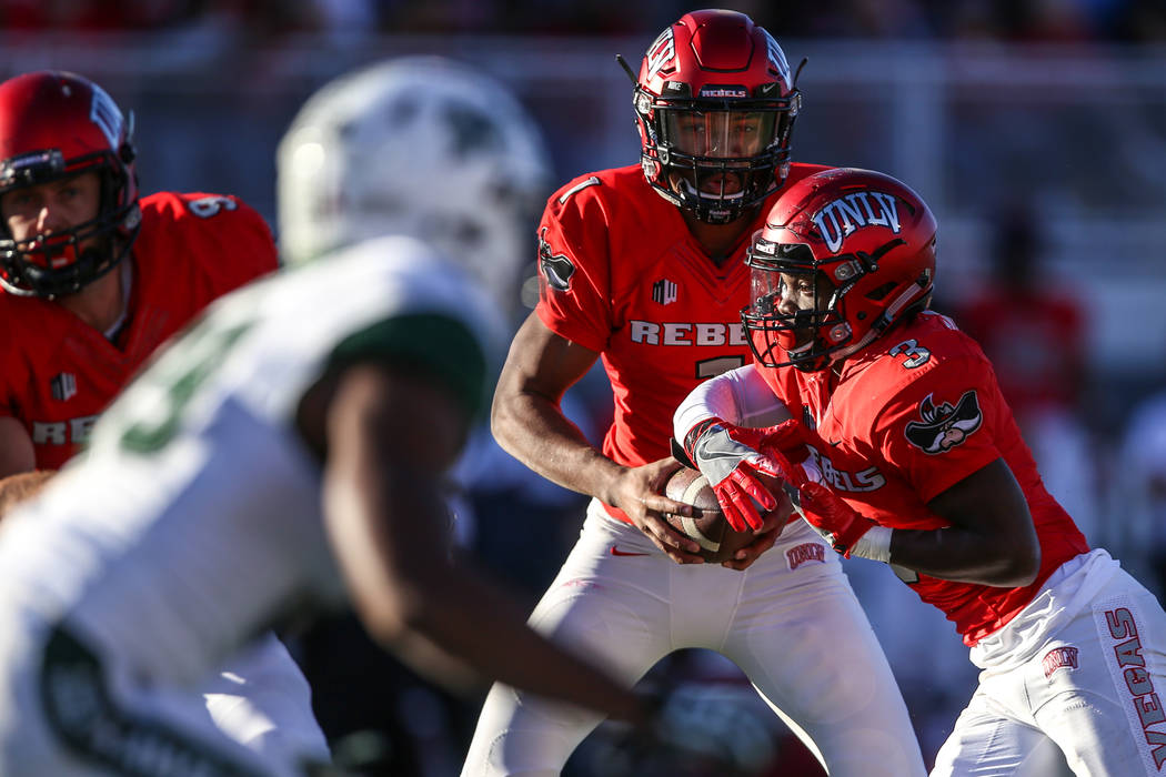 UNLV Rebels quarterback Armani Rogers (1), center, hands the ball off to UNLV Rebels running back Lexington Thomas (3), right, during the second quarter of a football game against the Hawaii Warri ...