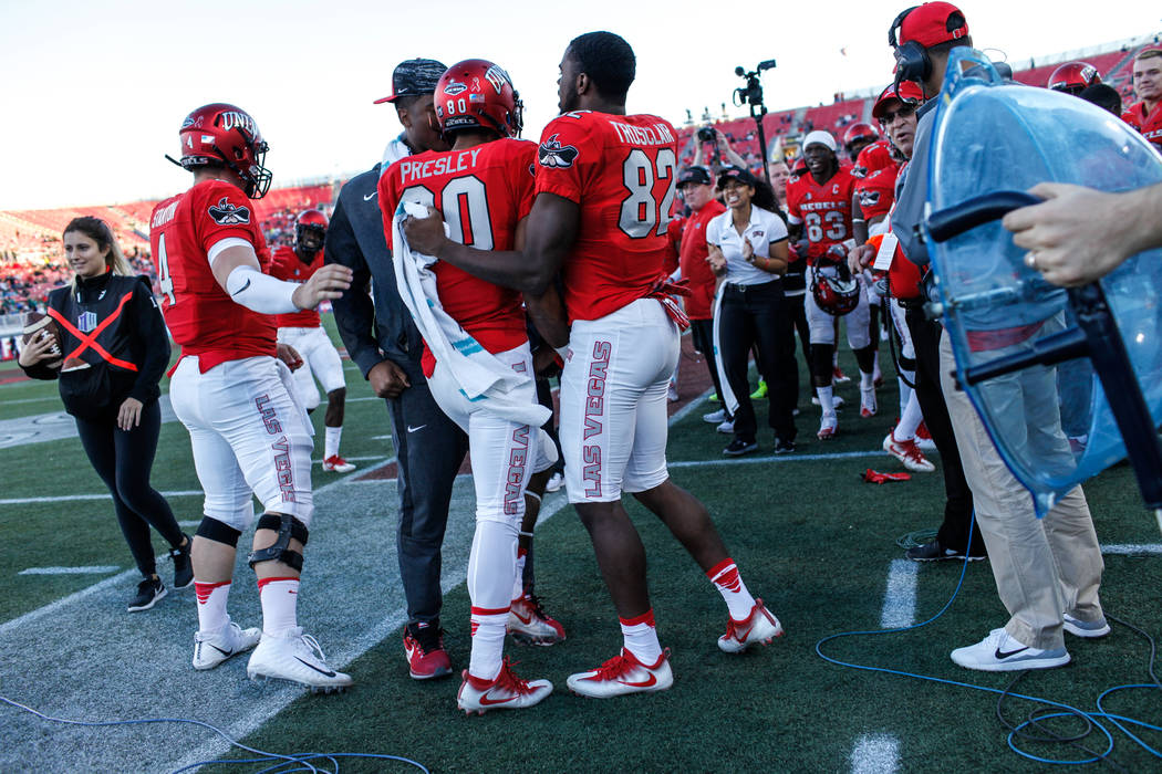 UNLV Rebels wide receiver Brandon Presley (80), center, is congratulated by teammates after scoring a touchdown against the Hawaii Warriors during the third quarter of a football game at Sam Boyd  ...