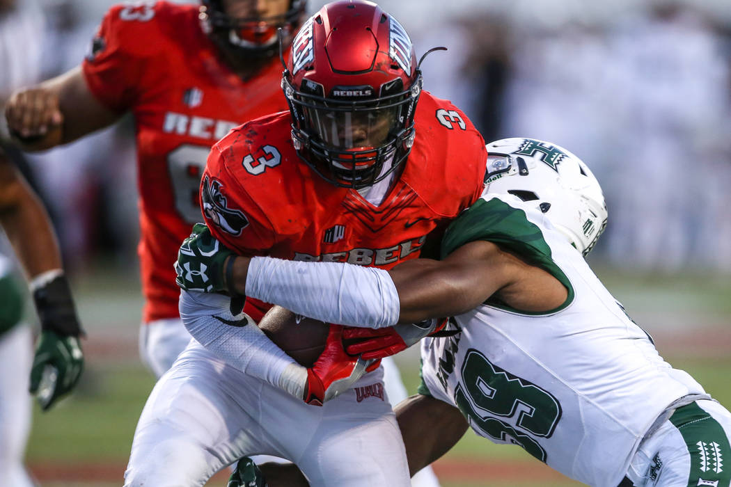 UNLV Rebels running back Lexington Thomas (3), left, runs the ball for a touchdown against against the Hawaii Warriors during the third quarter of a football game at Sam Boyd Stadium in Las Vegas, ...