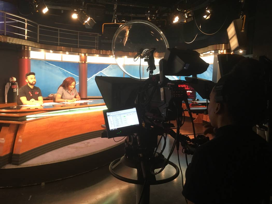 "Summer Crawley, foreground, operates a camera during filming of the semester's first ""Rebel Report"" episode Oct. 12. Behind the anchor desk are Alex Wong, left, and Arlynda Gregory. (Brian Sandfor ..."