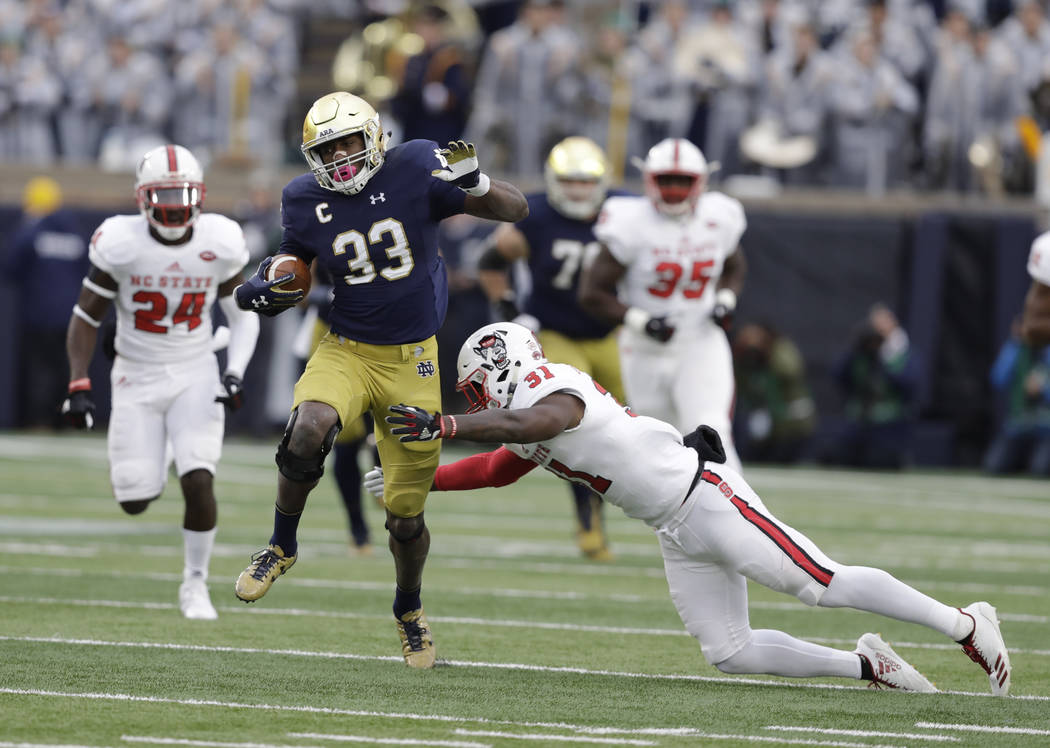 Notre Dame running back Josh Adams is tackled by North Carolina State safety Jarius Morehead (31) during the first half of an NCAA college football game, Saturday, Oct. 28, 2017, in South Bend, In ...