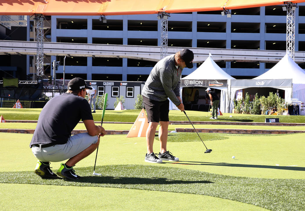 Jeff Gibralter, professional poker player, practice his putting as former Rebels golfer, Taylor Montgomery, looks on at Major Series of Putting Stadium on Saturday, Nov. 4, 2017, in Las Vegas. Biz ...