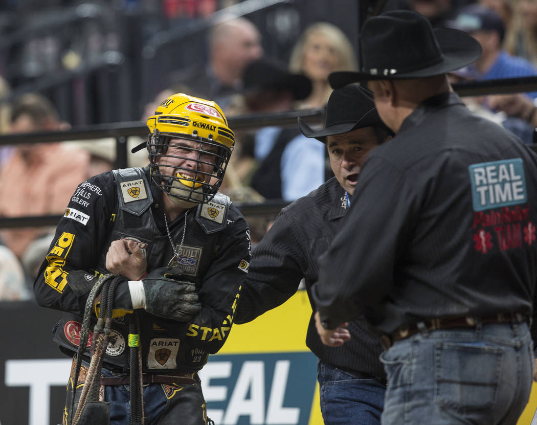 Matt Triplett is helped off the dirt after being hurt during his ride on Brutus during the Professional Bull Riders World Finals on Saturday, Nov. 4, 2017, at T-Mobile Arena, in Las Vegas. Benjami ...